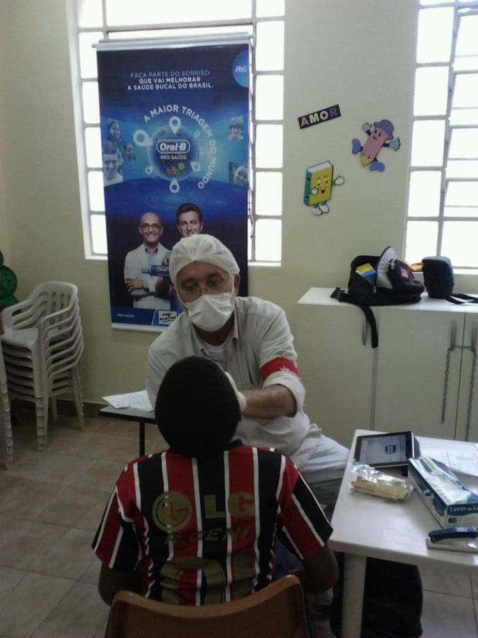 Dr. Luiz Scott, dentista voluntário, atendendo os adolescentes do Gol de Honra